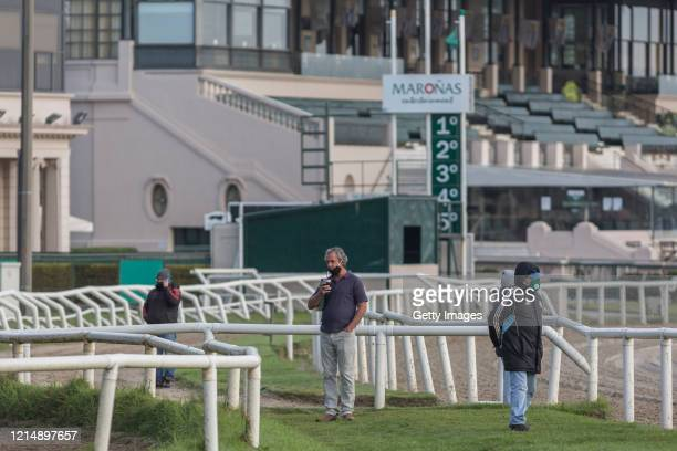 Horse owners watch the training during competition day as Uruguay slowly returns to normal due to coronavirus outbreak at Maroñas Horse Track on May...