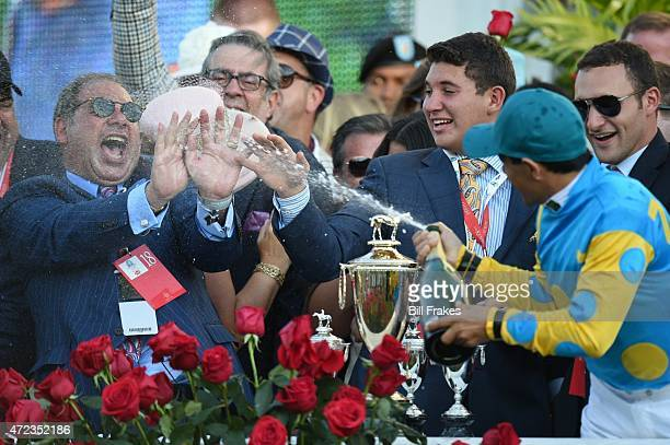 141st Kentucky Derby Victor Espinoza jockey for American Pharoah victorious spraying champagne onto owner Ahmed Zayat in Winner's Circle after race...
