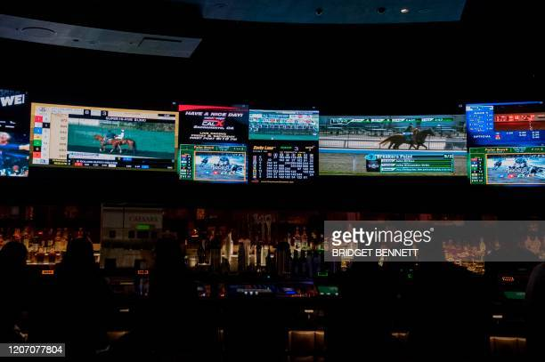 Horse racing is on display at a sports book at Caesars Palace Hotel and Casino in Las Vegas, Nevada on March 13 as some restaurants, and buffets...
