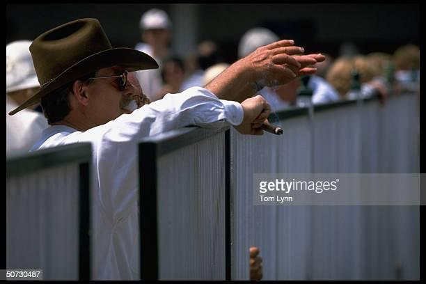 Kentucky Derby Fan smoking cigar against railing.