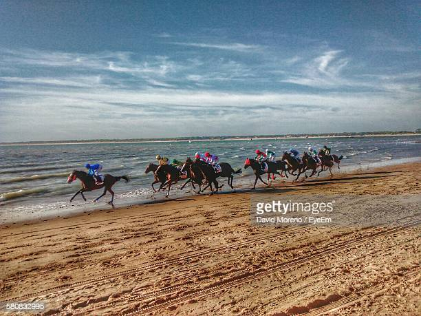 horse racing on beach against cloudy sky - horse racing ストックフォトと画像