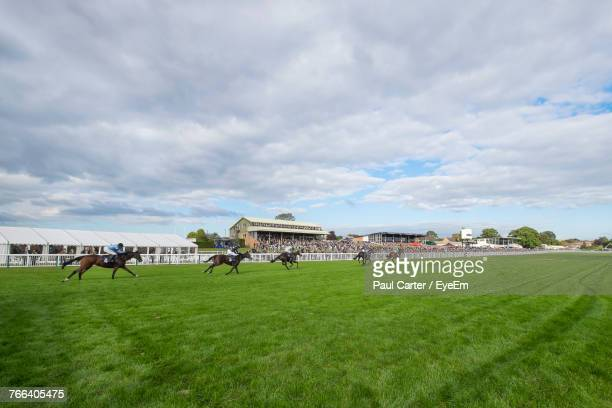 horse racing on grassy field against cloudy sky - horse racing stock pictures, royalty-free photos & images