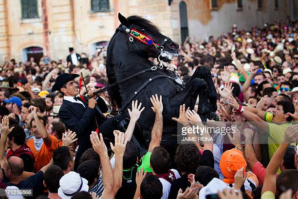 A horse rears in a crowd during a horse parade of the traditional San Juan festival in the town of Ciutadella on the Balearic Island of Menorca on...