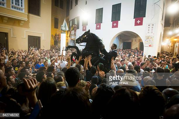TOPSHOT A horse rears in a crowd during the traditional San Juan festival in the town of Ciutadella on the Balearic Island of Menorca on the eve of...