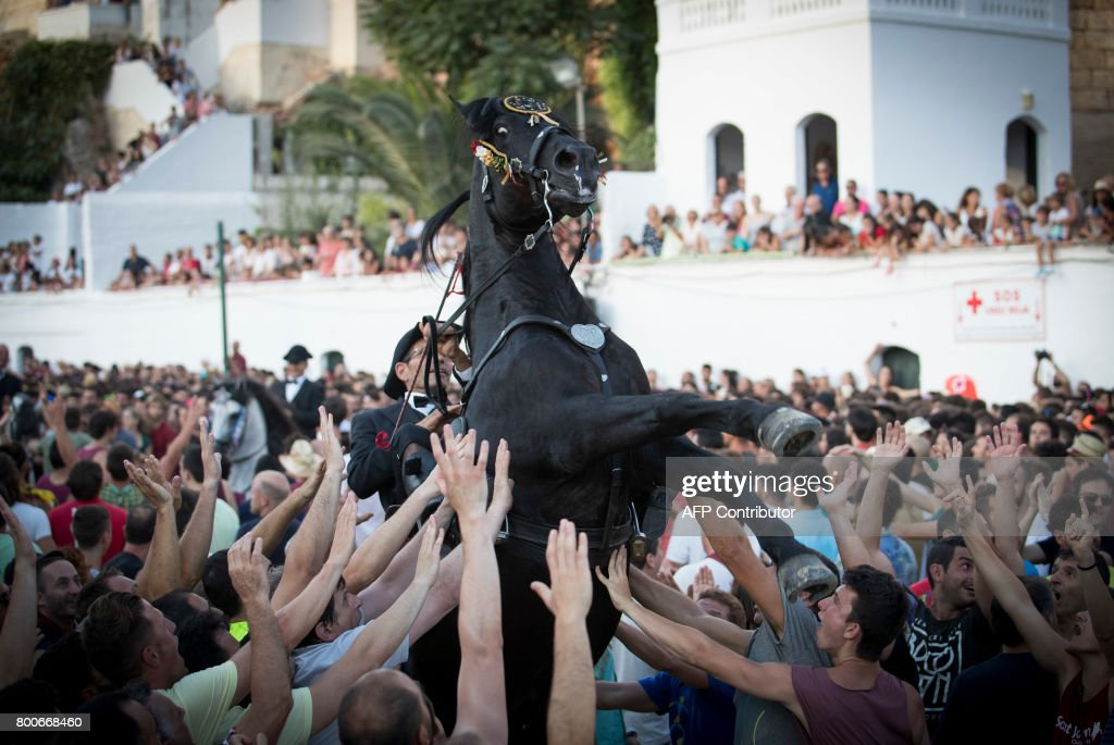a horse rears in the crowd during the traditional san juan festival