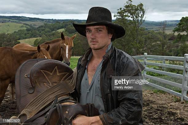 horse rider holding saddle with horses