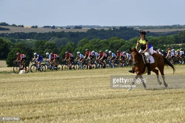 A horse rider is pictured in front of the pack riding during the 2135 km seventh stage of the 104th edition of the Tour de France cycling race on...