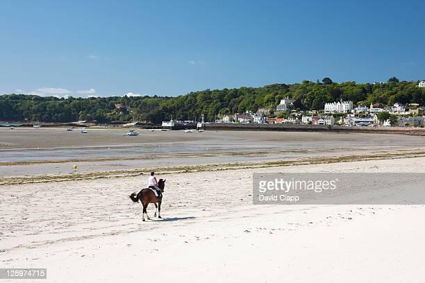 Horse rider on St Aubins Bay, in St Aubin in Jersey, Channel Islands