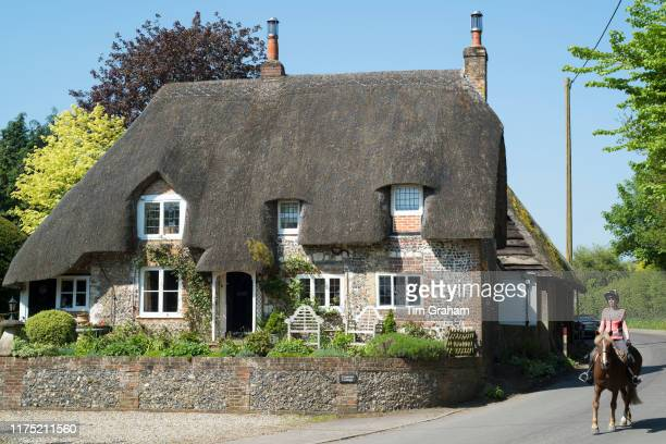 Horse rider passes typical English thatched cottage of brick and flint construction in Ramsbury Wiltshire United Kingdom