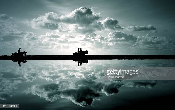 horse riders reflected in pool - camber sands stock photos and pictures