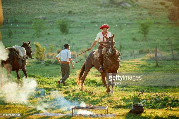 horse riding after an argentinian barbecue. - argentina stock pictures, royalty-free photos & images
