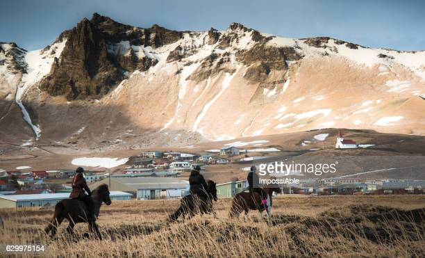 horse riding at vik black beach with the vik village at the background in winter