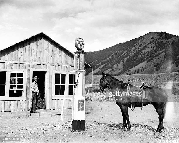 A horse stands by a Conoco gas pump as if waiting for refueling outside the William D Kahler store in Challis National Forest Idaho | Location Lost...