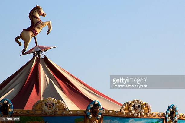 Horse Statue On Roof Of Carousel Against Clear Blue Sky