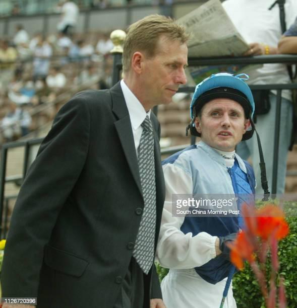Horse trainer John Size accompanies winning jockey Shane Dye to scale after John's trained horse Darwin ridden by Shane Dye won the Race 8 at Sha Tin...