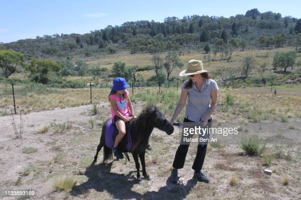 Horse trainer leading a young girl on a pony horse