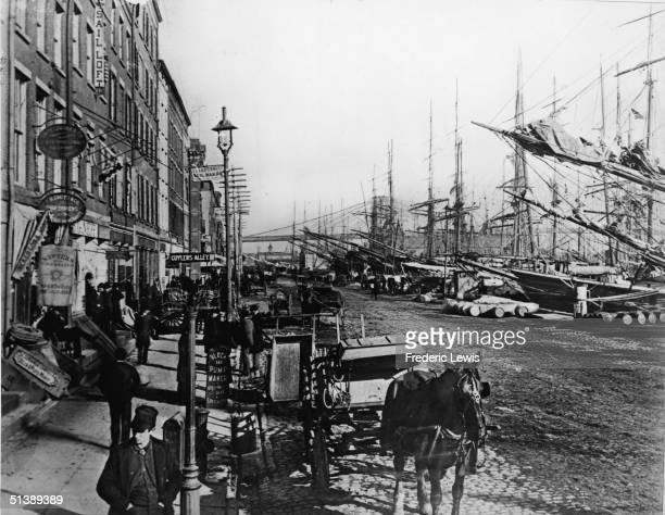 Horse waits on a cobblestone street across from sailing ships docked at the South Street waterfront on the East River in New York City, 1883. In the...