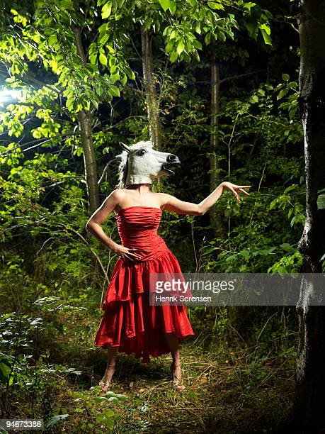 Horse woman standing in red dress in forest