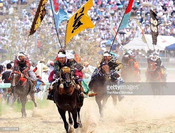 Horseback riders in fullbody armor compete during the 'Soma Nomaoi Festival' on July 23 2012 in Minamisoma Fukushima Japan Some 400 riders...