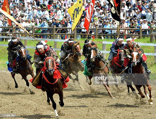 Horseback riders in full-body armor compete during the 'Soma Nomaoi Festival' on July 23, 2012 in Minamisoma, Fukushima, Japan. Some 350 riders...