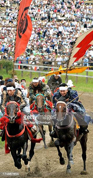 Horseback riders in fullbody armor compete during the 'Soma Nomaoi Festival' on July 23 2012 in Minamisoma Fukushima Japan Some 350 riders...