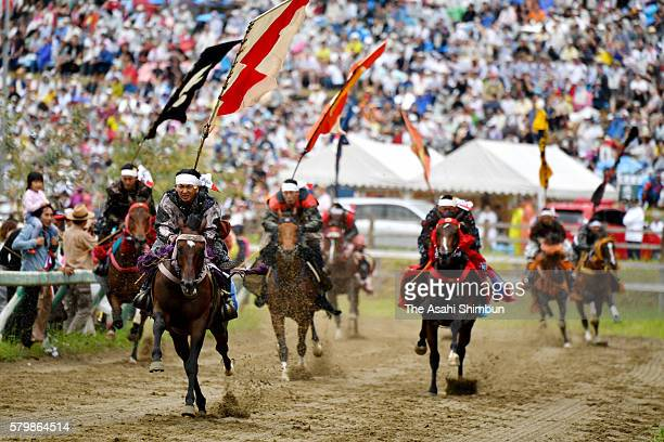Horseback riders in fullbody armor compete in the 'Kacchu keiba' horse racing during the 'Soma Nomaoi Festival' on July 24 2016 in Minamisoma...