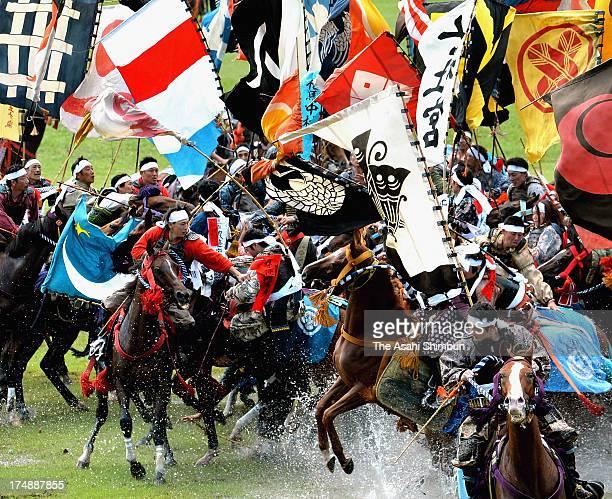 Horseback riders in fullbody armor compete in the 'Shinki Sodatsusen' pursuit of the Goshinki 'sacred flag' during the 'Soma Nomaoi Festival' on July...