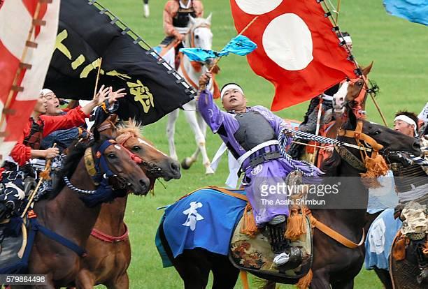 Horseback riders in full-body armor compete in the 'Shinki Sodatsusen', pursuit of the Goshinki 'sacred flag' during the 'Soma Nomaoi Festival' on...
