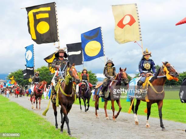 Horseback riders in fullbody armor enter the field prior to the 'Soma Nomaoi Festival' on July 30 2017 in Minamisoma Fukushima Japan