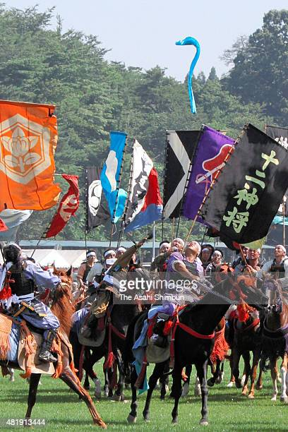 Horseback riders in fullbody armours compete in the 'Shinki Sodatsusen' pursuit of the Goshinki 'sacred flag' during the 'Soma Nomaoi Festival' on...