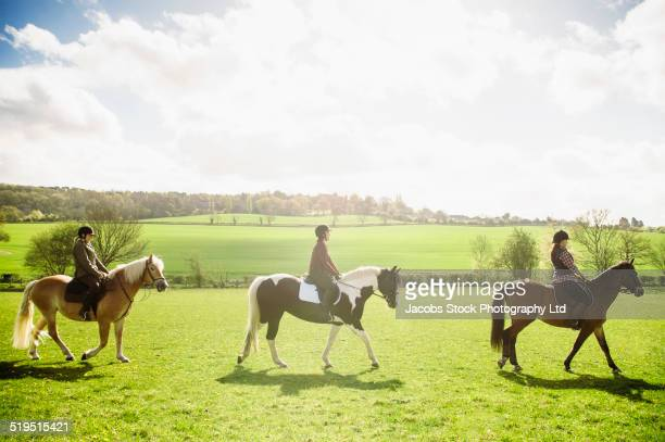 horseback riders in rural field - recreational horseback riding stock pictures, royalty-free photos & images