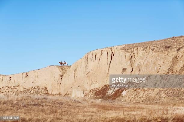 Horseback Riders On A High Ridge and Cliffs