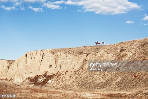 Horseback Riders On A High Ridge Riding Away