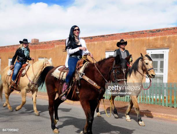 Horseback riders ride along Canyon Road in Santa Fe New Mexico Canyon Road is popular with visitors and art enthusiasts because of its dozens of...