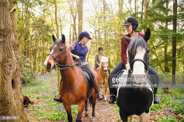 Horseback riders talking in forest
