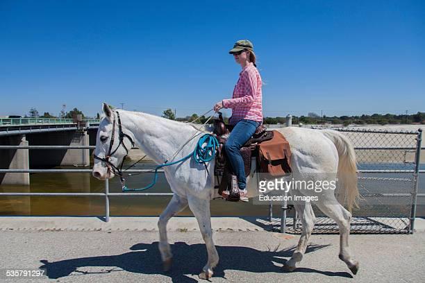 Horseback riding near Del Amo Blvd, Los Angeles River, Long Beach, Los Angeles County, California, USA.
