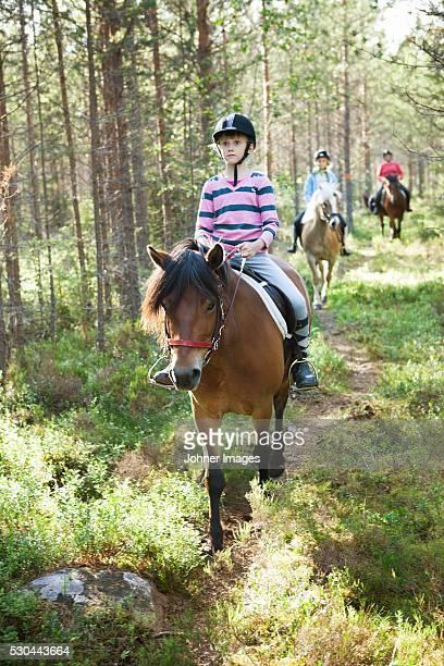 horseback riding through forest - paardrijden stockfoto's en -beelden