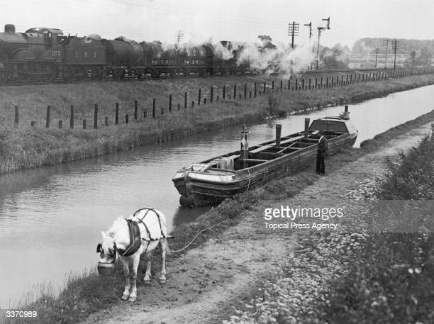 A horsedrawn barge moored on the Oxford Canal at Brinklow in Warwickshire June 1936 The owner watches an LMS train speed by at a very different pace