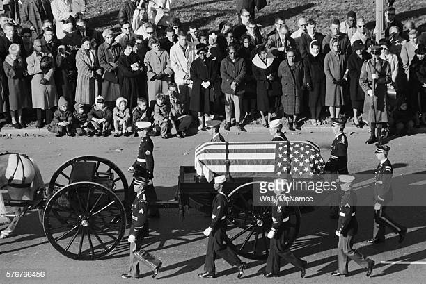 A horsedrawn caisson carrying the body of John Fitzgerald Kennedy passes mourners lining the streets of Washington from the White House to the Capitol