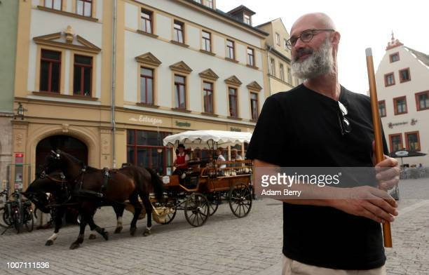 A horsedrawn carriage passes as a Klezmer musician performs on Herderplatz square during Yiddish Summer Weimar on July 28 2018 in Weimar Germany The...
