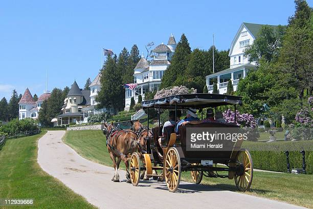 A horsedrawn carriage passes by the mansions overlooking Lake Huron on West Bluff Road at Mackinac Island Michigan