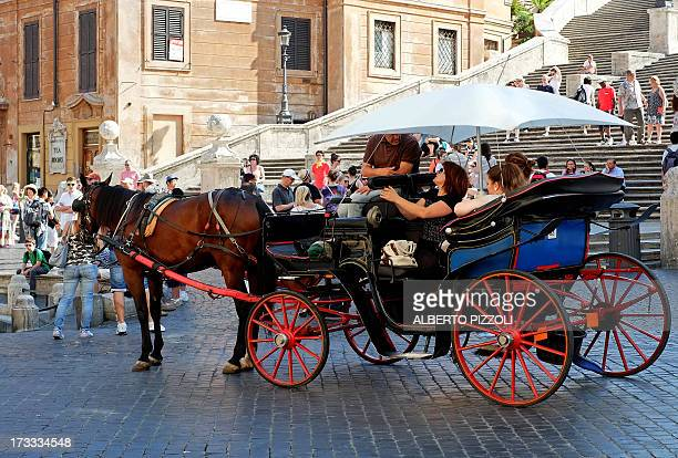 A horsedrawn carriage used for riding tourists in the city passes by the Spanish steps piazza di Spagna on July 12 2013 in Rome In order to protect...