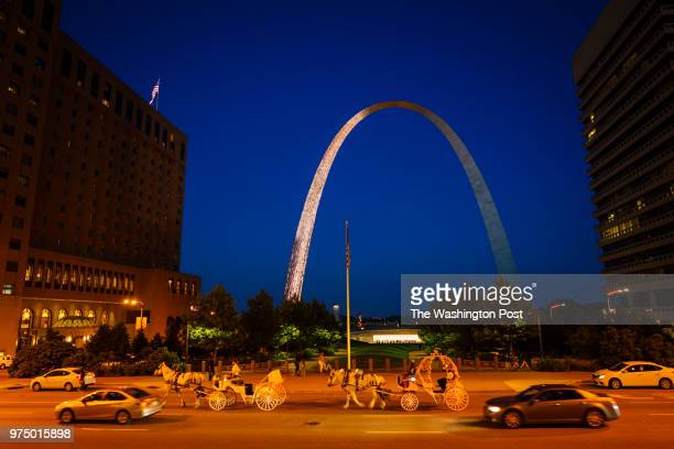 Horsedrawn carriages and cars share the road near the Gateway Arch near the Mississippi River in downtown St Louis Missouri on June 1 2018 The Arch...