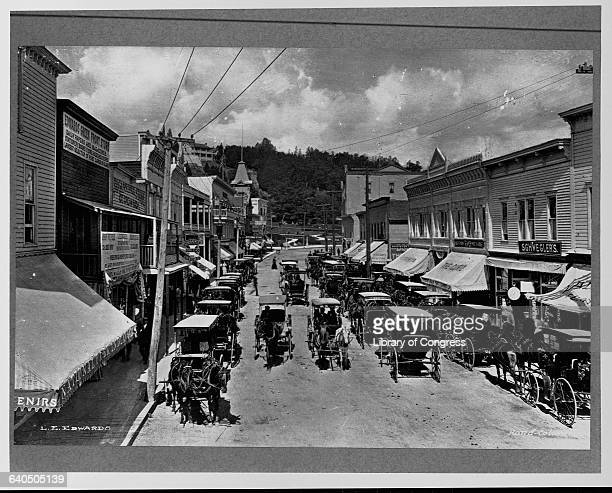 Horsedrawn carriages file past Main Street storefronts on Mackinac Island in Michigan