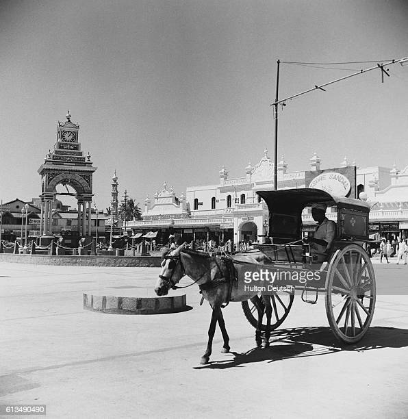 A horsedrawn cart passes through a city square in the center of which stands an arched clock tower