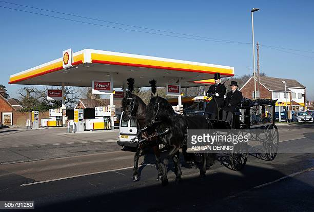 Horse-drawn funeral carriage passes a Royal Dutch Shell petrol station in Hook, near Basingstoke on January 20, 2016. Royal Dutch Shell said it...