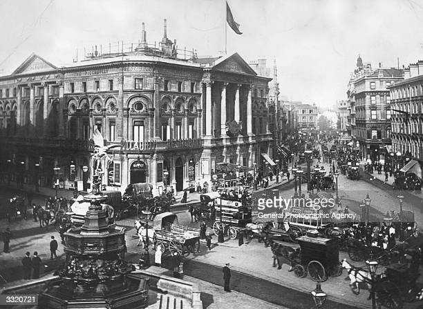 Horsedrawn traffic and passersby outside The London Pavilion at Piccadilly Circus The statue of Eros is on the left