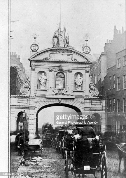 Horsedrawn traffic passes through Temple Bar the gateway between the Strand and Fleet Street London 1872 The lettering strung across the arch reading...