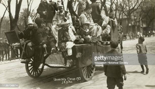 A horsedrawn wagon filled with University of Wisconsin students dressed as clowns proceeds along a Madison street as part of a parade Madison...