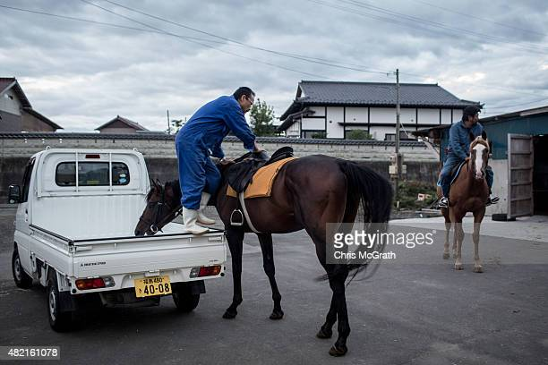 Horseman climbs onto his horse during a training session ahead of the Soma Nomaoi festival on July 24, 2015 in Minamisoma, Japan. Every summer the...